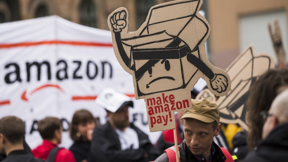 People hold banners during a demonstration attended from Amazon-Workers, trade union members and left activits under the motto 'Make Amazon Pay' in Berlin, Germany on April 24, 2018.