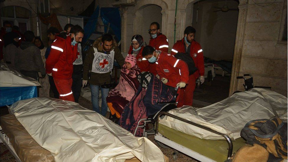 Girl in a wheelchair, being pushed away by Red Cross and Red Crescent doctors through beds with dead bodies in an old people's home in eastern Aleppo, Wednesday 7 December 2017