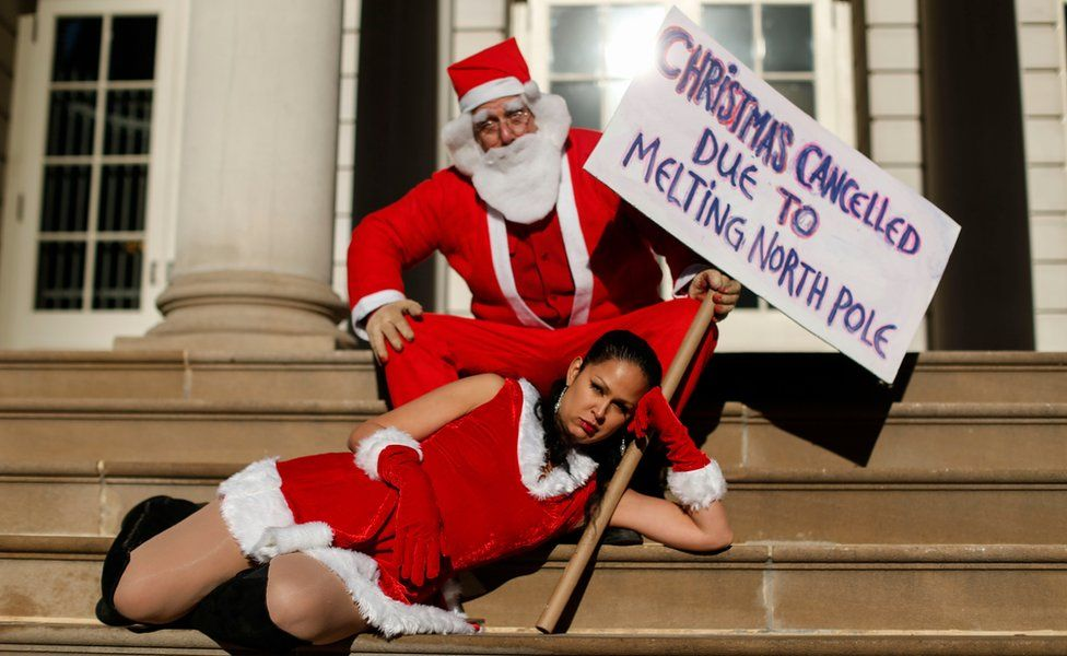 Activists dress up as Santa Claus holds a banner as he takes part in a global climate march at City Hall on November 29, 2015 in New York City.