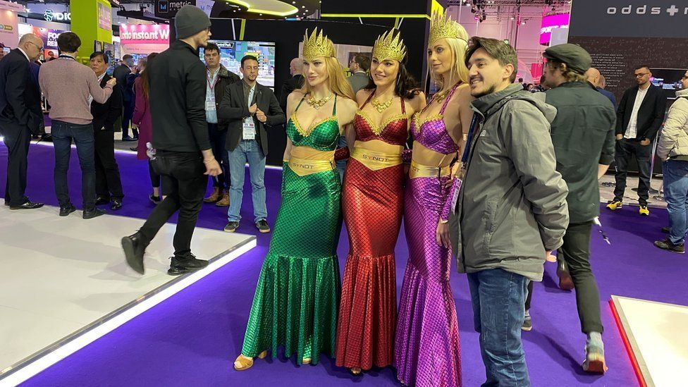Flavio Grasselli stands with three women dressed as mermaids