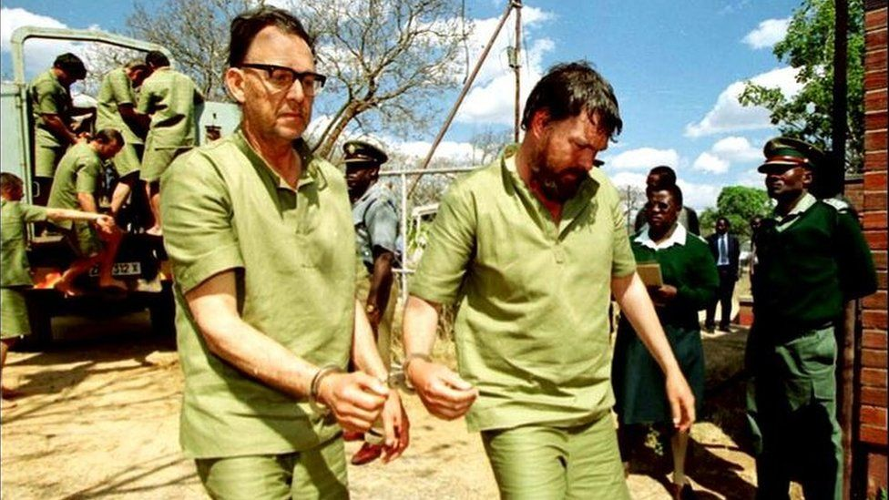 Two white Zimbabwean farmers handcuffed together arrive at a court in Chinhoyi, Zimbabwe, in 2001