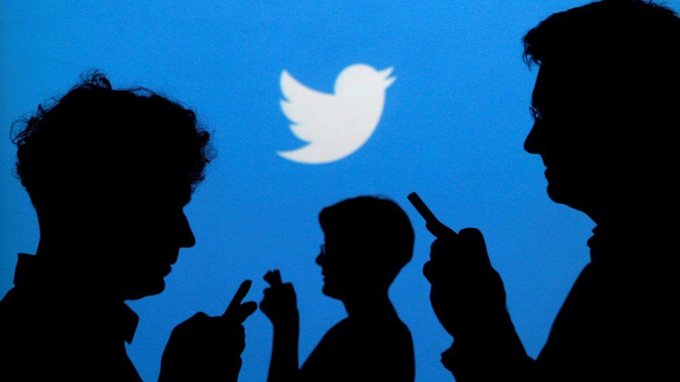 Twitter logo on a screen with the silhouettes of people on their phones in front of it