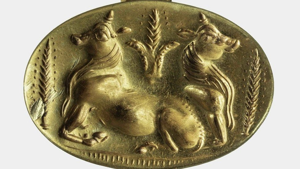 Gold ring depicting two bulls and sheaves of barley