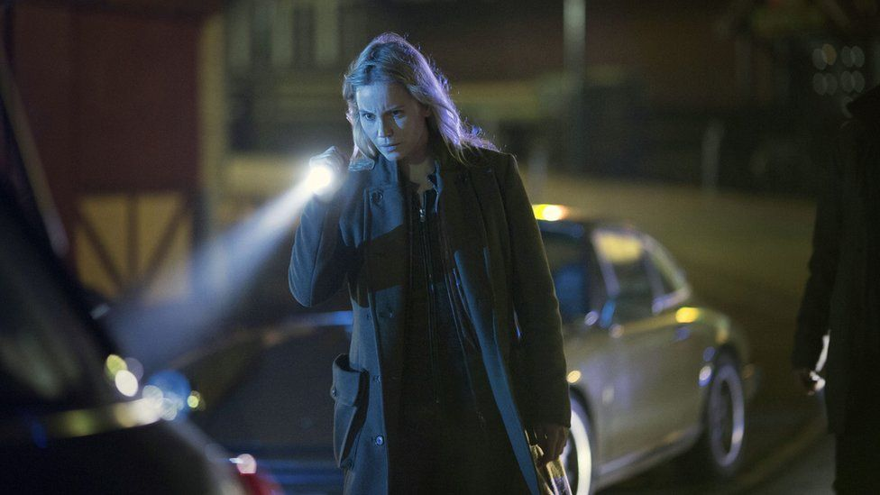 Saga in a still from The Bridge, at night holding a torch
