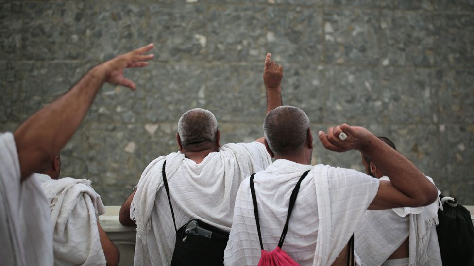 Pilgrims cast stones at one of the pillars, 2015