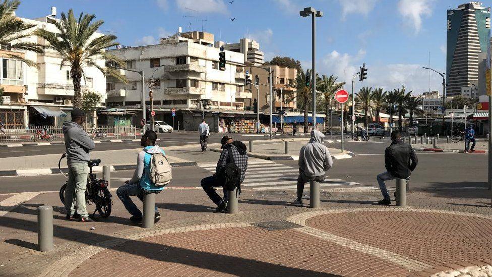 Men sit on bollards in Tel Aviv