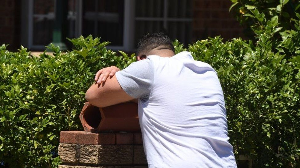 A man with his head in his arms at the scene