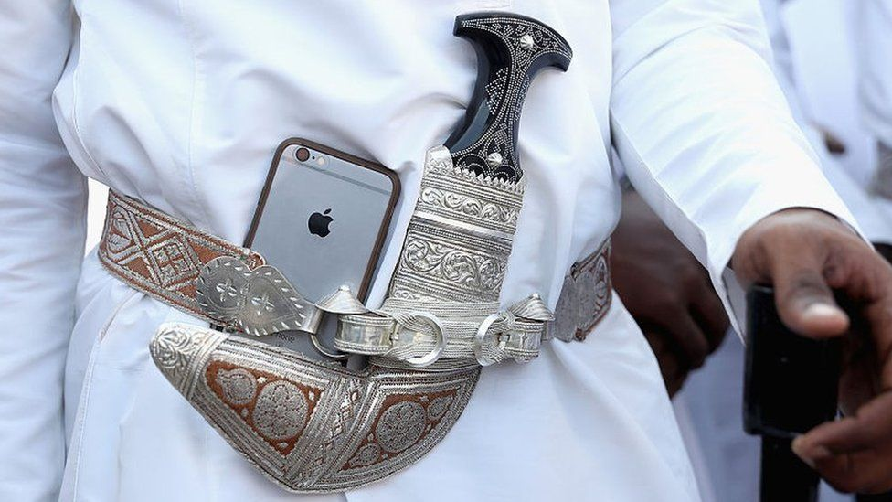 A dancer tucks his Apple iPhone next to his traditional Omani dagger during a welcome ceremony in Muscat, Oman (5 November 2016)