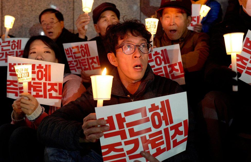 """South Koreans with candles and placards reading """"Park Geun-Hye Out"""" shout slogans during a rally against South Korean President Park Geun-Hye on a main street in Seoul, South Korea, 21 November 2016."""