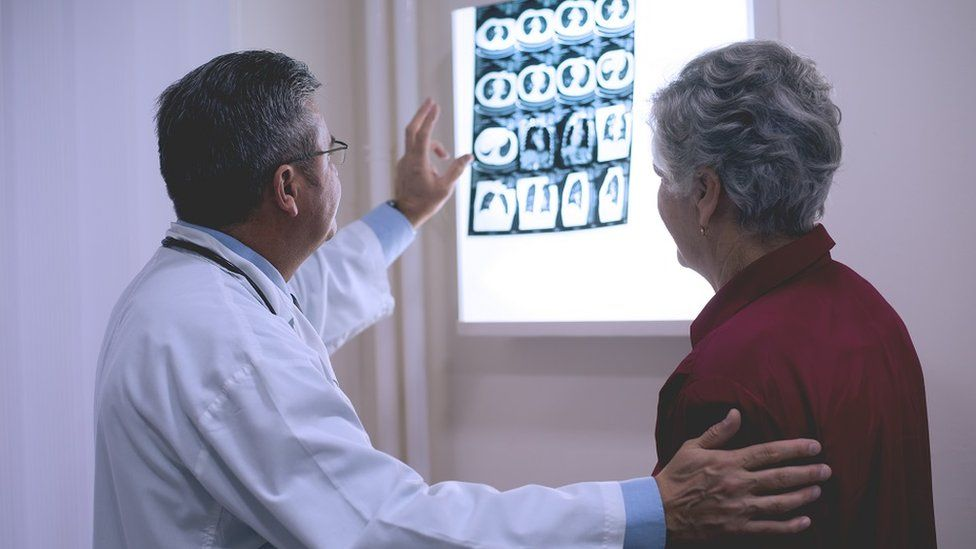 Doctor discussing x-ray with patient