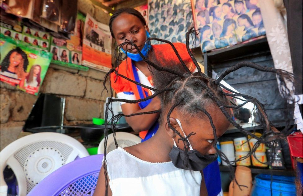A child has her hair threaded in a salon in Kenya's capital, Nairobi - 29 April 2020