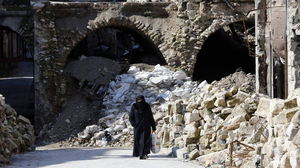 A woman walks past debris in the Syrian city of Aleppo (12 February 2019)