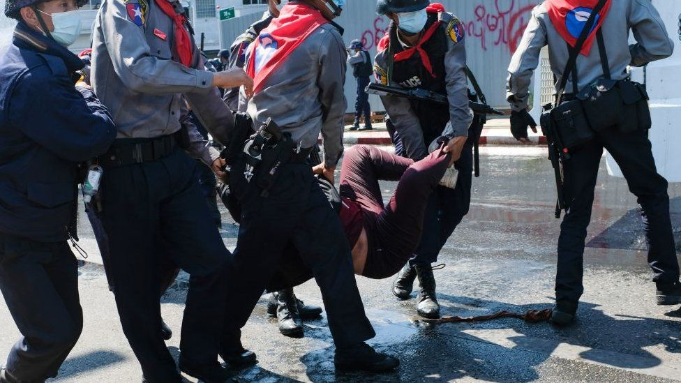 Police carry a protester