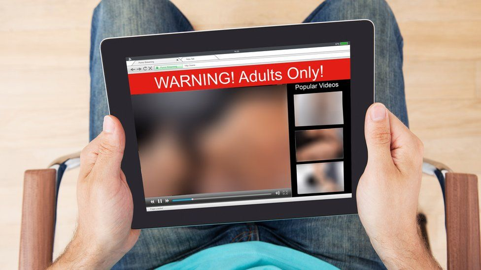 A man looking at a tablet with blurred sexual images on