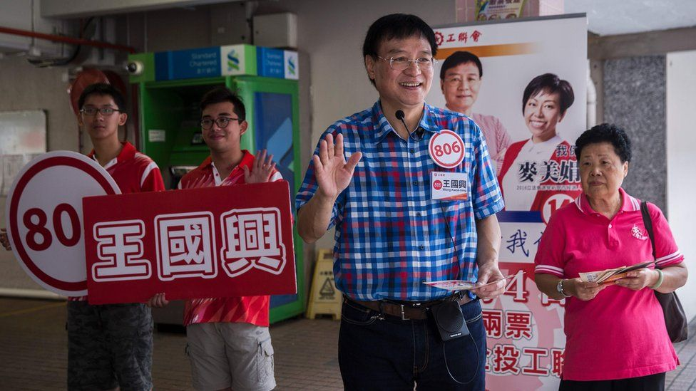 This picture taken on August 30, 2016 shows pro-Beijing candidate Wong Kwok-hing from the political party Hong Kong Federation of Trade Unions, waving while campaigning at Kwai Shing West Estate in Hong Kong ahead of the legislative council elections