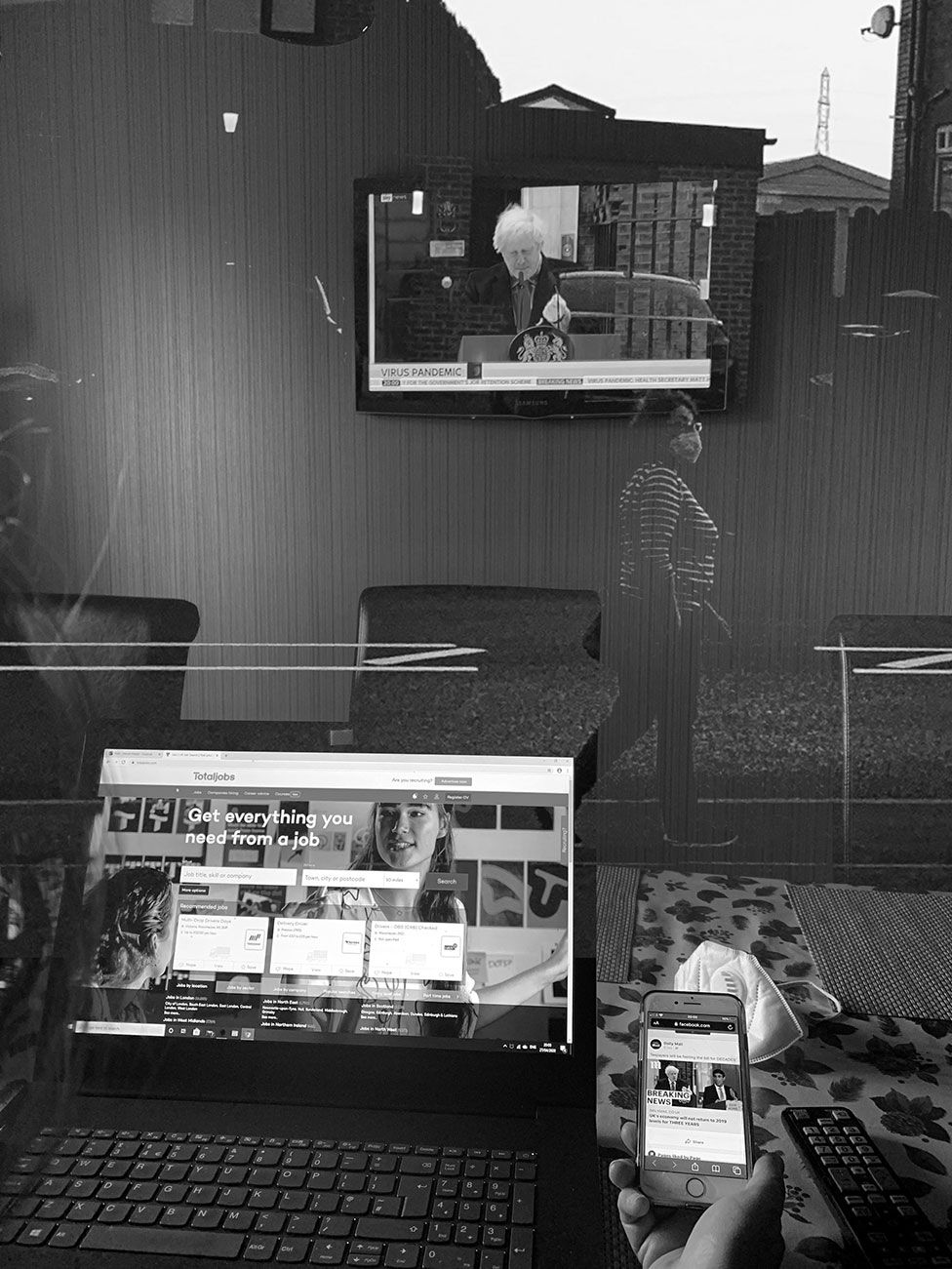 A black-and-white montage of a laptop, phone, television and woman walking past wearing a face mask