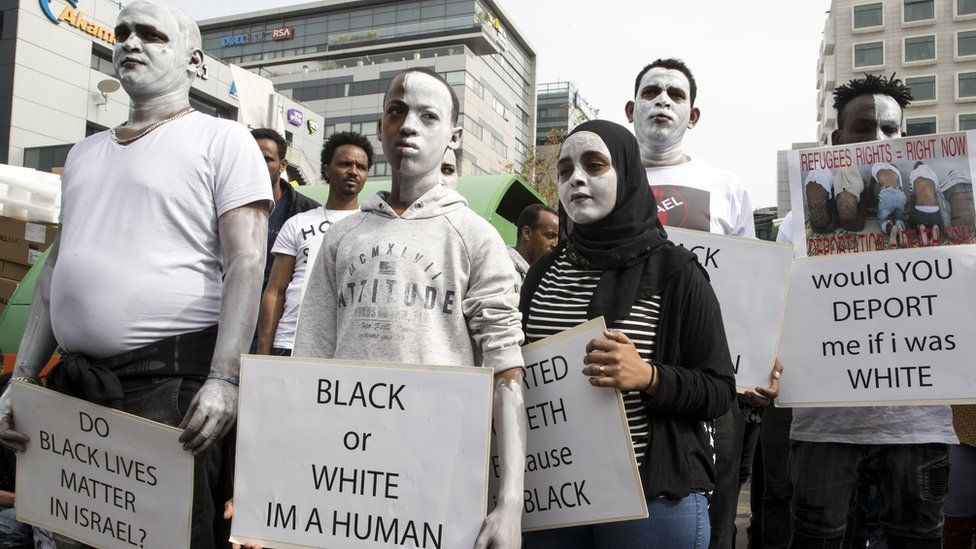 African migrants demonstrate with white paint on their faces, outside the Embassy of Rwanda in the Israeli city of Herzliya on February 7, 2018, against the Israeli government's policy to forcibly deport African refugees and asylum seekers to Rwanda and Uganda.