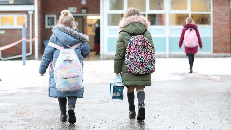 Girls walking towards a school