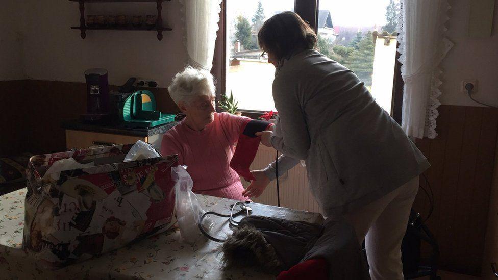 A community nurse treats a patient