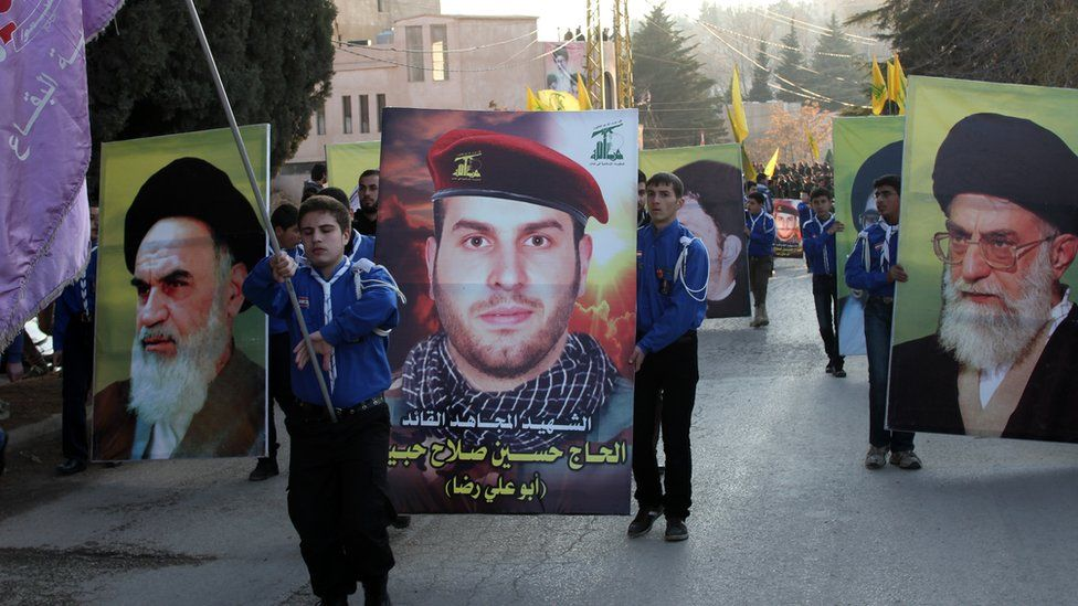 Banners showing the founder of the Islamic Republic of Iran, Ayatollah Ruhollah Khomeini (L), and the current Supreme Leader of Iran, Ayatollah Ali Khamenei (R), are held up beside one of a Lebanese Hezbollah commander killed in Syria (C) at a funeral in Baalbek (1 January 2014)