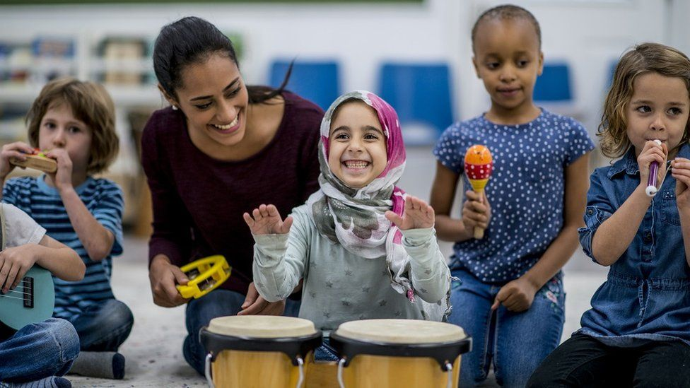A multi-ethnic group of young school children are indoors in their classroom, playing instruments.