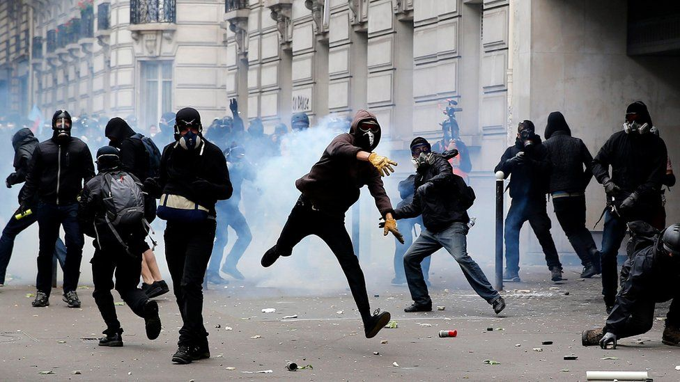 A protester throws back a tear gas canister during clashes with riot police during a national demonstration and strike against the Labour Law reform in Paris, France, 14 June 2016