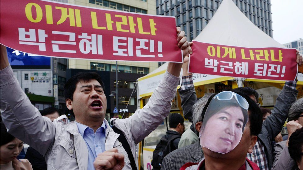 """A protester (right) wears a cut-out photograph of Choi Soon-sil while another demonstrator holds a banner reading """"President Park Geun-hye's resignation"""" in Seoul on 27 October 2016"""