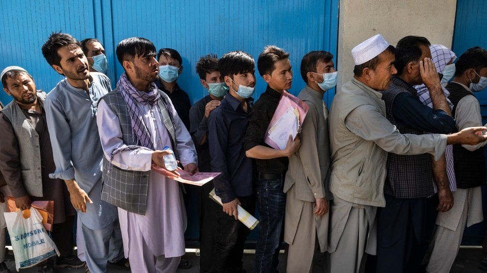Afghans wait in long lines for hours at the passport office as many are desperate to have their travel documents ready to go on August 14, 2021 in Kabul, Afghanistan.