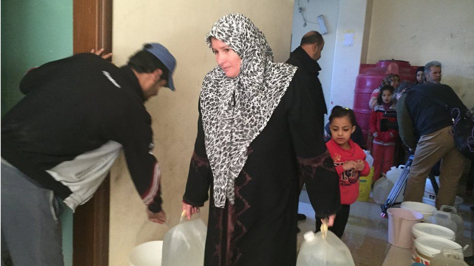 Woman carrying large bottles of water