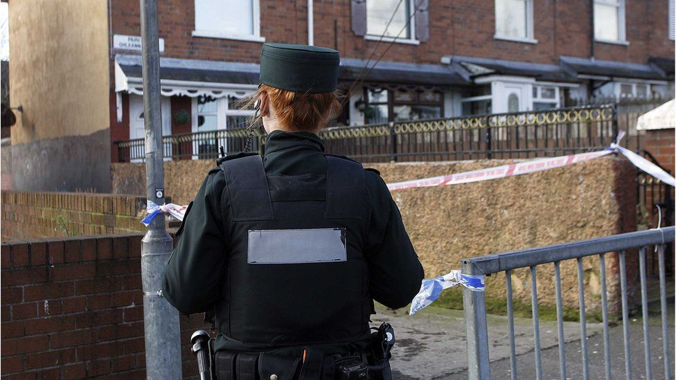 Police remain at the scene of the shooting in north Belfast