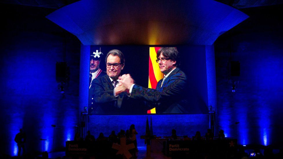 Catalonia's leader, Carles Puigdemont (R), on a big screen. projected into a Barcelona event, 13 January 2018