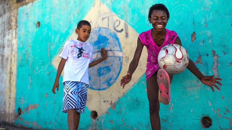 A boy and girl play football in the Chacara do Ceu favela