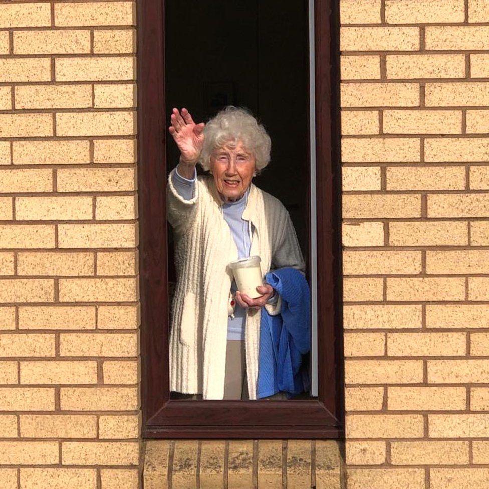 Lady waving at window