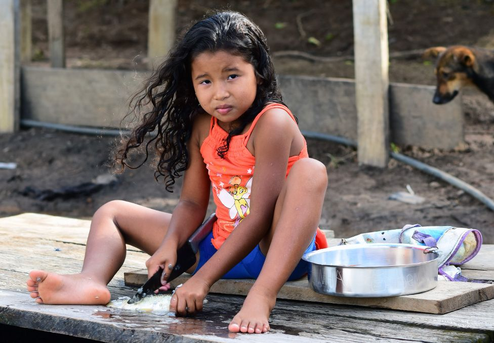 A girl prepares fish at the banks of the river