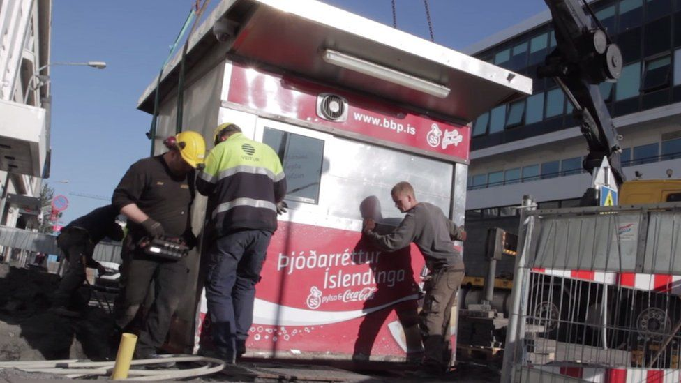 Workmen lift the Baejerins Beztu hot dog stand