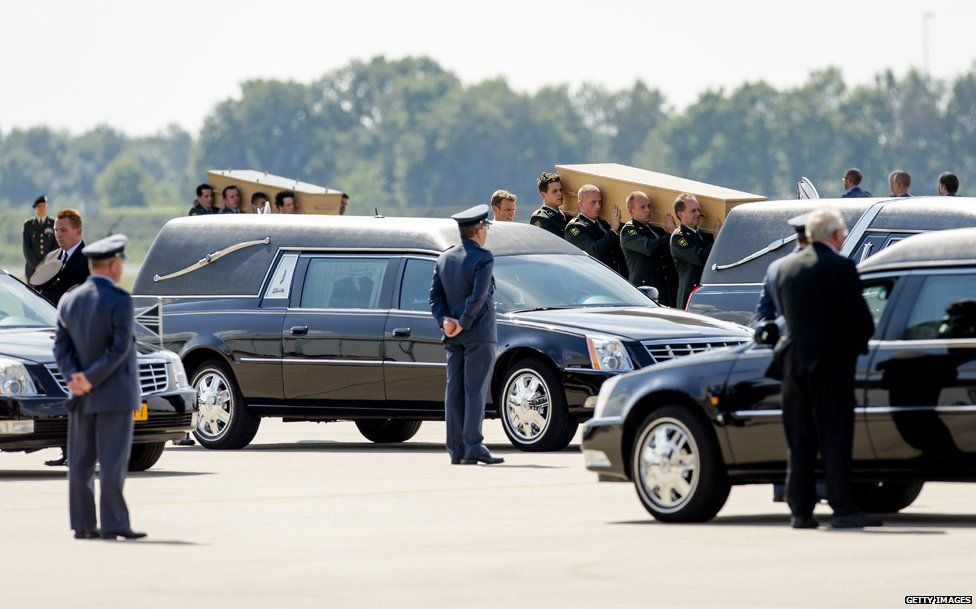 Dutch military personnel carry coffins containing the remains of the victims of the MH17 plane crash to a waiting hearse at the airbase in Eindhoven on July 24, 2014.
