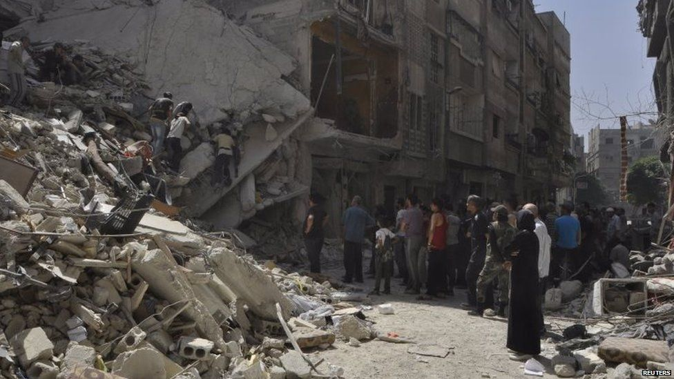 Palestinian refugees inside the Yarmouk refugee camp in Damascus inspect damage caused by what they said was a barrel bomb dropped by Syrian government forces (26 May 2015)