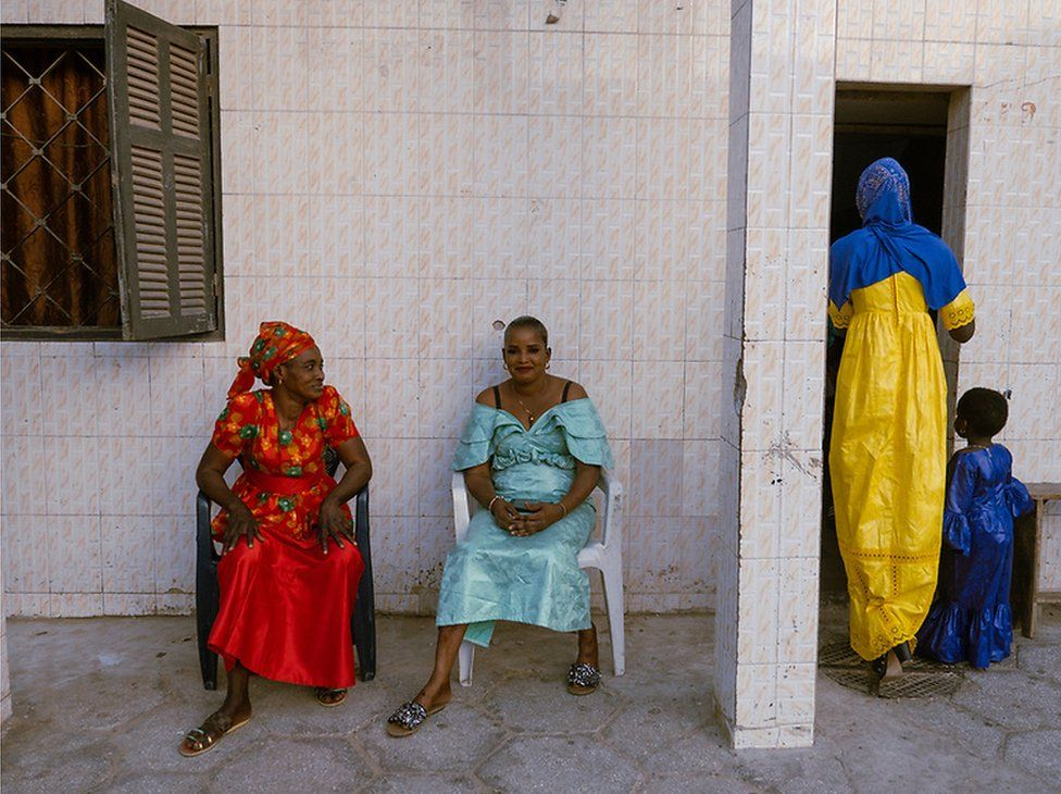 Khady Diouf wears a red dress and Aissatou Cissé is in blue. They sit outside on chairs