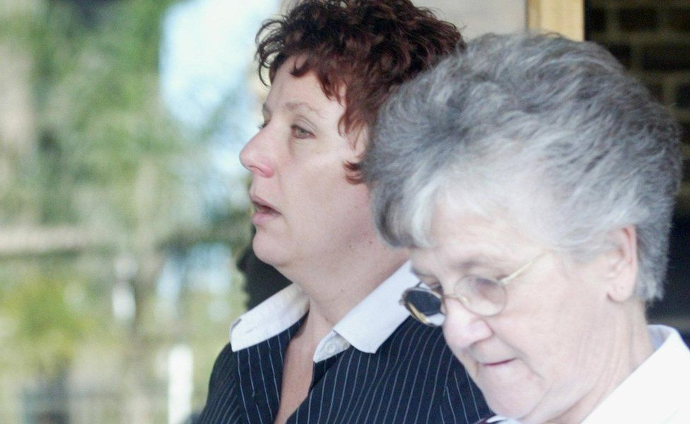 Kathleen Folbigg leaves Darlinghurst Court during her trial during April 2003 with the support of Salvation Army major and support worker Joyce Harmer