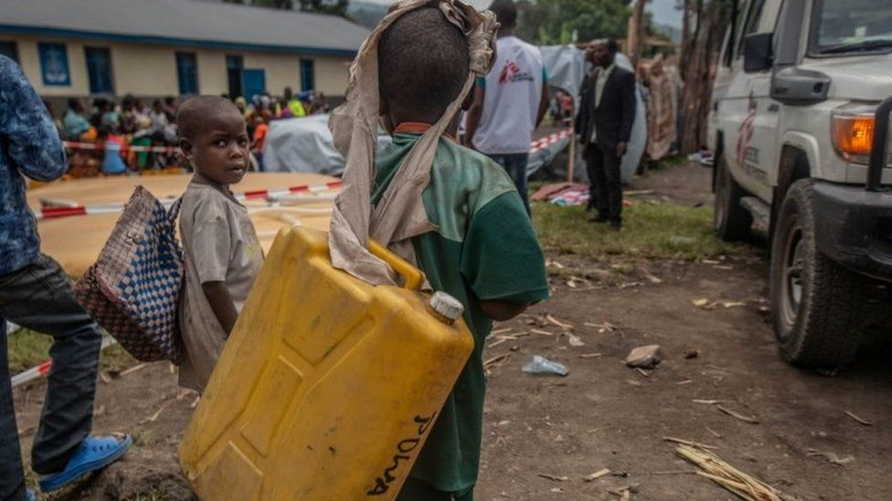 Displaced children wait to get drinking water at a distribution point near their temporary camp in Sake, eastern DR Congo. Photo: 28 May 2021