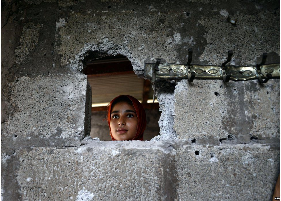 A Pakistani Kashmiri, affected by cross border firing, shows the damaged wall hit by mortar shell at her home in Dhair Bazar, Madarpur sector on the on the Line of Control (LoC), some 150 kilometres from Muzaffarabad, capital of Pakistan administered Kashmir on 8 August 2015.
