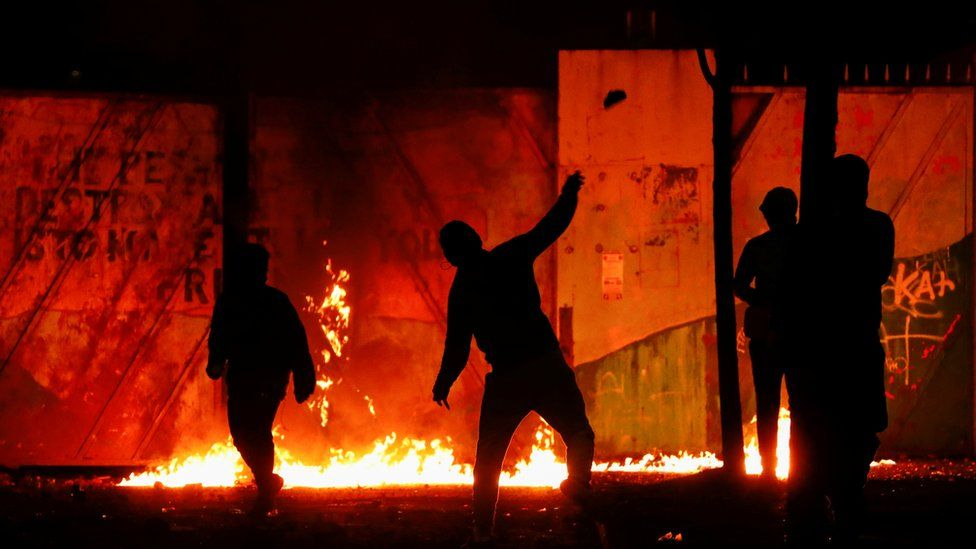 """Rioters are seen at the """"peace wall"""" gate into Lanark Way as protests continue in Belfast,"""