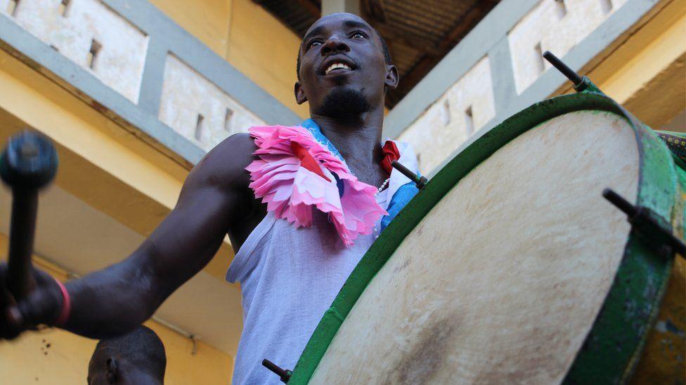 Man prepares to hit a drum hanging vertically from his shoulder in Sekondi Ghana