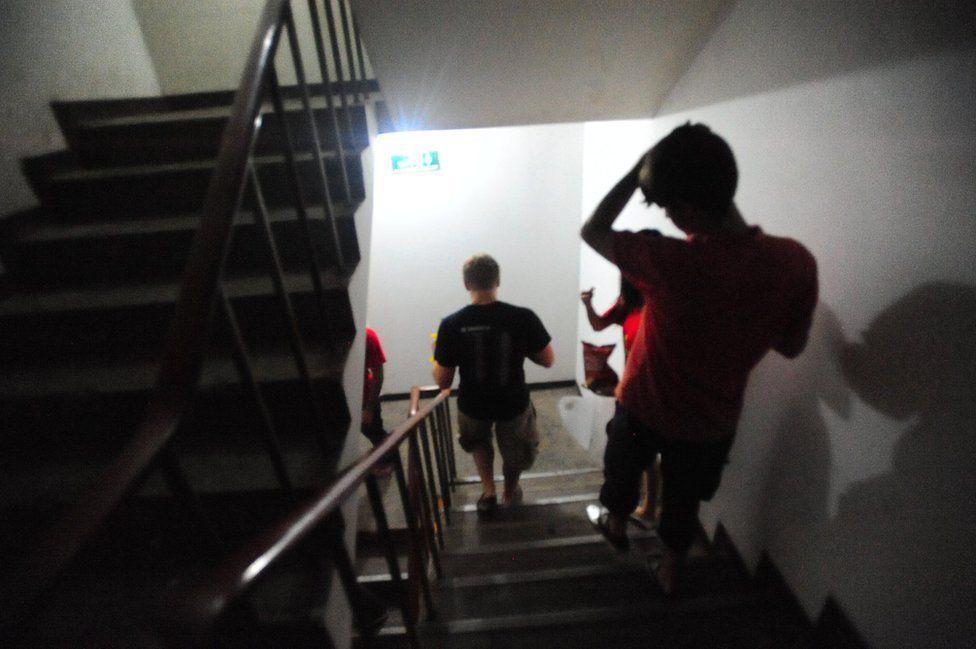 Calvin Sun y sus amigos bajan las escaleras del hotel