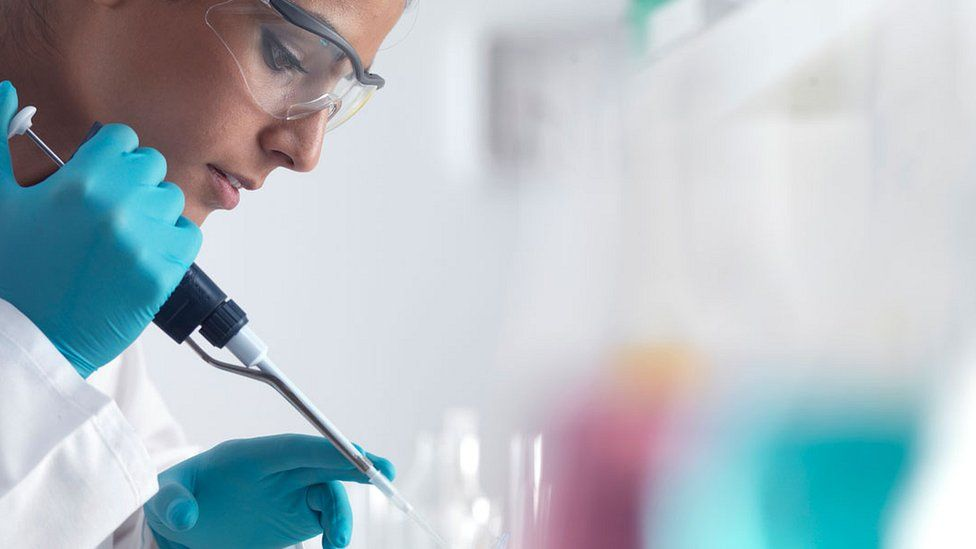researcher in goggles and gloves with pipette