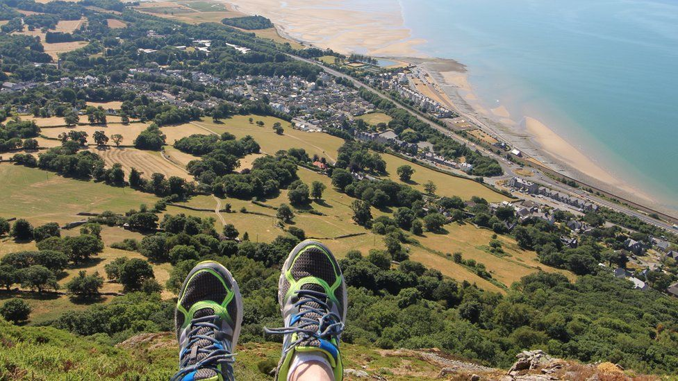 Alan's feet appear in the bottom of the picture which looks out high over the community below and the shoreline
