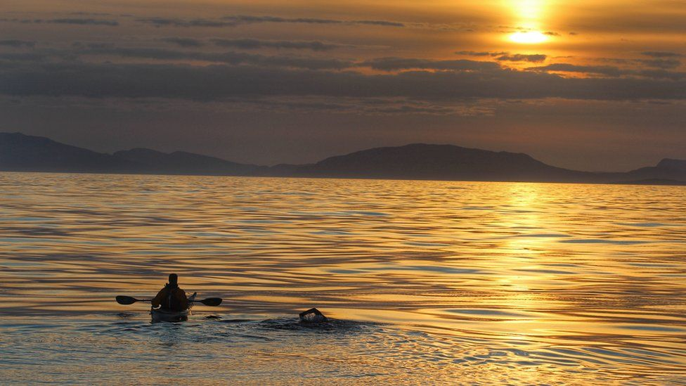 Kayaker and swimmer