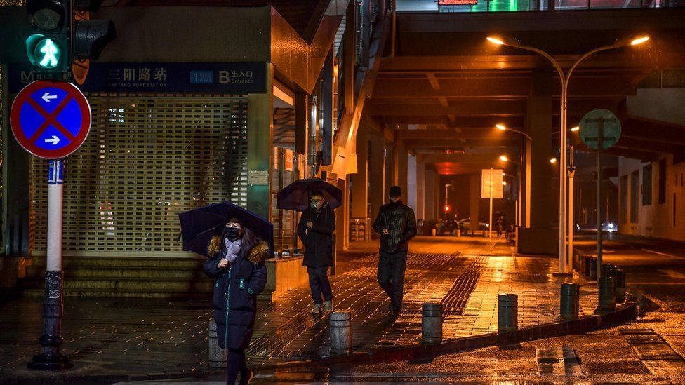 People in protective masks walk on a street in Wuhan