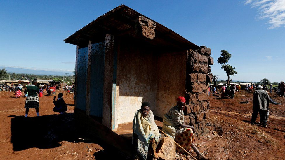 Survivors sit outside their destroyed house after a dam burst, which unleashed water at nearby homes, in Solio town near Nakuru, Kenya on 10 May 2018