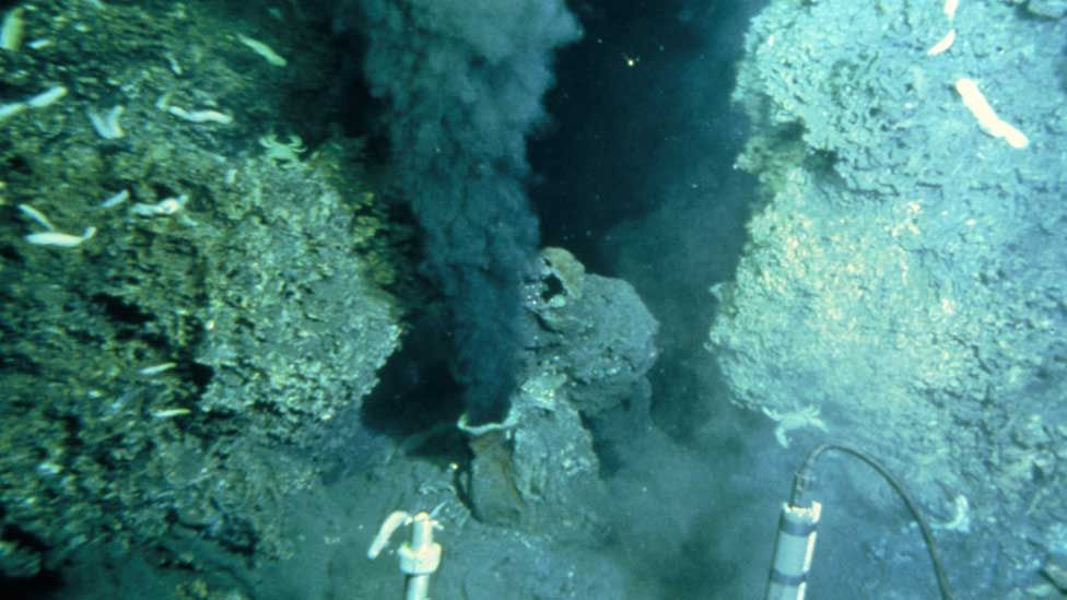 """View from a deep sea vehicle of the billowing black """"smoke"""" being emitted by a hydrothermal vent on the ocean floor. Known as a """"black smoker"""", this sulphurous mineral-rich fluid pours out of a sulphur-encrusted mound or chimney."""